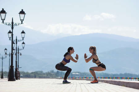 Two girls doing sports with resistance bands, on the promenade by the sea and mountains in the background.