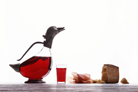 Decanter with wine in the form of ducks, glass with wine, Parma ham and expensive blue cheese. On white background. Stock Photo