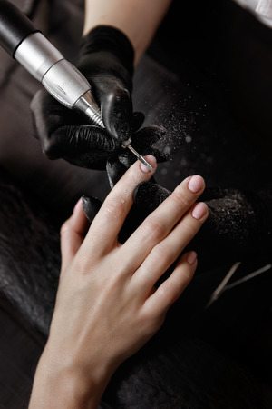 Manicurist in black gloves, grinding machine removes old gel Polish. Prepares for nail extension.  Spa facilities. Manicure room. Stock Photo