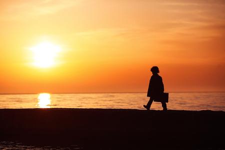Een kleine jongen in een jas met een koffer, wandelen langs de pier bij zonsondergang. Kleine reiziger. Toerisme. Vintage. Ontsnap uit huis. Silhouet.