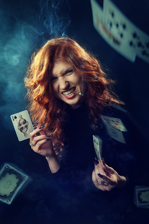 The red-haired fortune-teller smokes a cigar and predicts the future, laughs, throws cards. Queen of spades. Mysticism, occultism, Tarot, numerology.