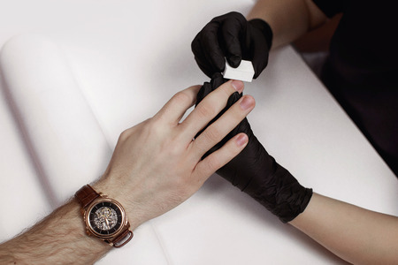 The man on procedures in manicure salon. Spa, manicuring, processing of nails nail file buff. Beautiful male hands.