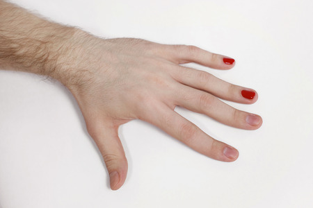 The man in manicure salon. A male hand with the made-up nails, gel varnish of red color.