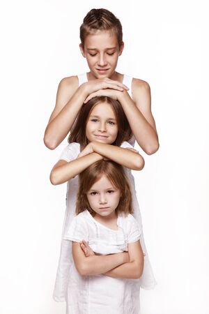 Three children in the studio on a white background, a brother and two sisters, put their hands on each other s head, stand the tower, indulge. Happy, healthy childhood. Banco de Imagens