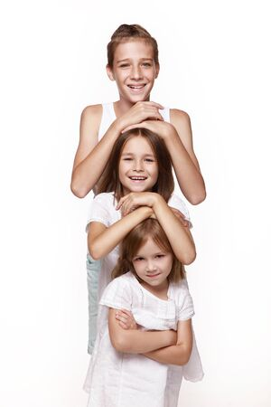 Three children in the studio on a white background, a brother and two sisters laugh, put their hands on each other 's head, indulge. Happy, healthy childhood.