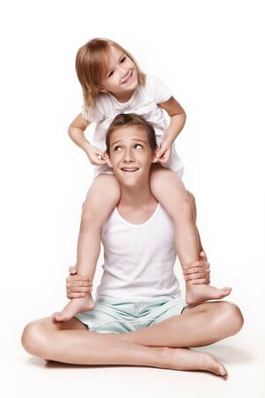 The sister sits on her brother 's neck and pulls his hands by his ears, everyone laughs, plays together. In the studio on a white background. Happy childhood.