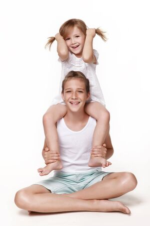 The sister sits on her brother 's neck and pulls herself with her hands by the scallops, everyone laughs, pampers, plays together. In the studio on a white background. Happy childhood.
