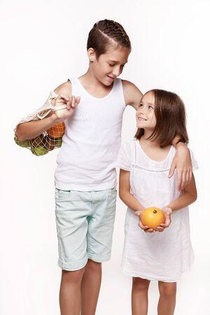 スタジオで、白い背景に果物と軽い服を着た兄弟姉妹。バッグ、オレンジ、適切な食べ物。