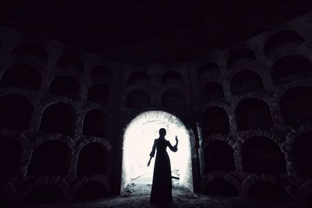 The silhouette of the girl in the dress standing in the opening from which there is a bright light. Stone wine cellar.