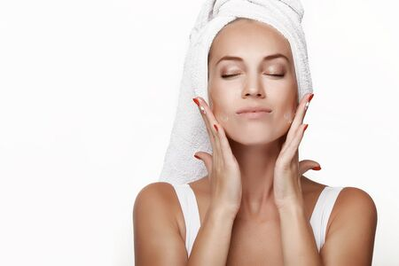 A beautiful young girl in a white blouse with a towel on her head, after a shower, applies cream to her face, makes a massage and laughs. Moistens a face with cream. Spa. In the studio on a white background.