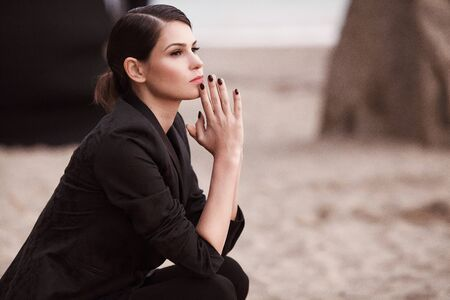 A beautiful young girl in a black suit, retro image, sits on a chair, on the beach