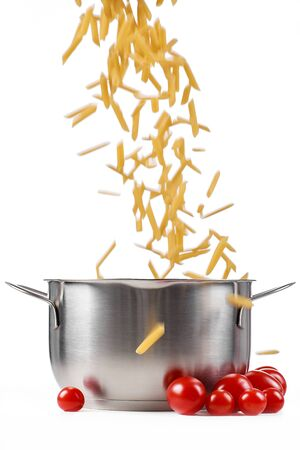Raw pasta poured into a saucepan on a white background.