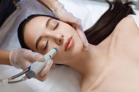 Professional female cosmetologist doing hydrafacial procedure in Cosmetology clinic. Banque d'images
