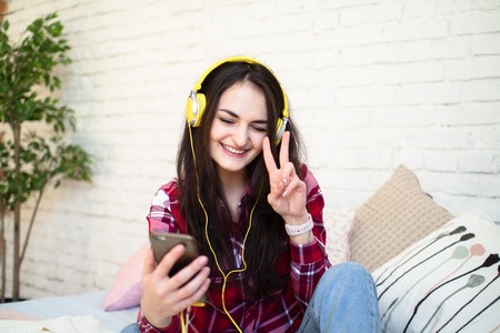 Happy pretty woman in earphones listening to music and singing while sitting on bed and holding mobile phone