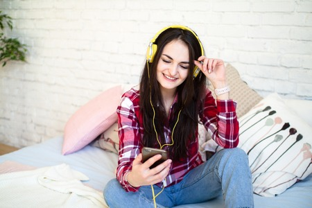 Portrait of beautiful woman in morning listening music sitting on bed at home Фото со стока