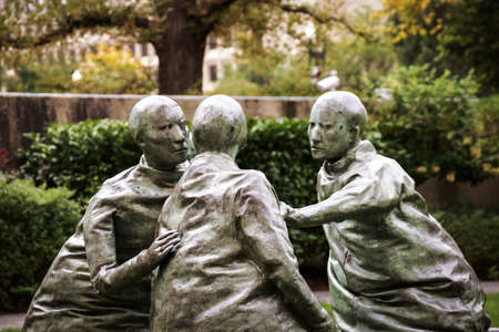 whose: Public sculpture of three talking men whose bodies, resemble punching bags