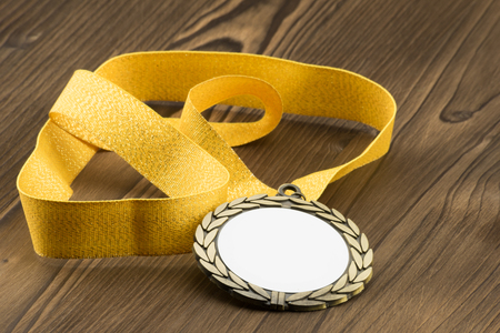 Gold medal with white placeholder and yellow ribbon on wooden textured table