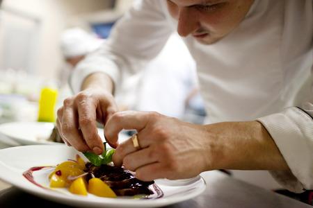 chef: Cocinero es decorar delicioso plato, desenfoque de movimiento en manos Foto de archivo