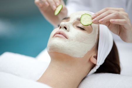 treatments: Beautiful young woman receiving facial mask of cucumber in beauty Stock Photo