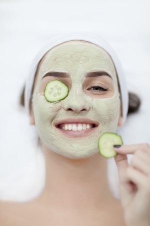 Mooie jonge vrouw die gezichtsmasker van komkommer in beauty Stockfoto