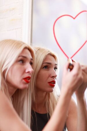 woman mirror: Young woman drawing heart on mirror with Stock Photo