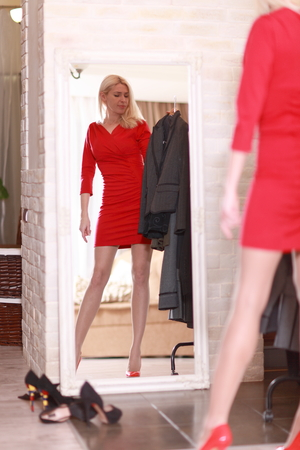 Woman trying red dress shopping for clothing. Beautiful happy smiling young shopper woman looking in mirror standing in clothes store. photo