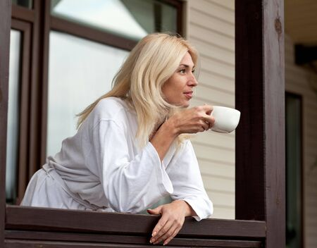 porch scene: Young Woman Drinking Morning Coffee on Porch Stock Photo
