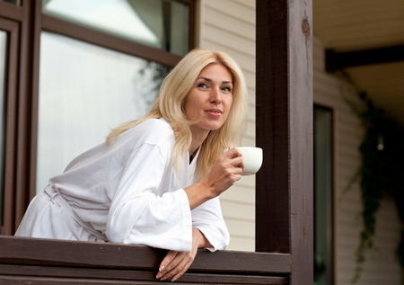 stoop: Young Woman Drinking Morning Coffee on Porch Stock Photo