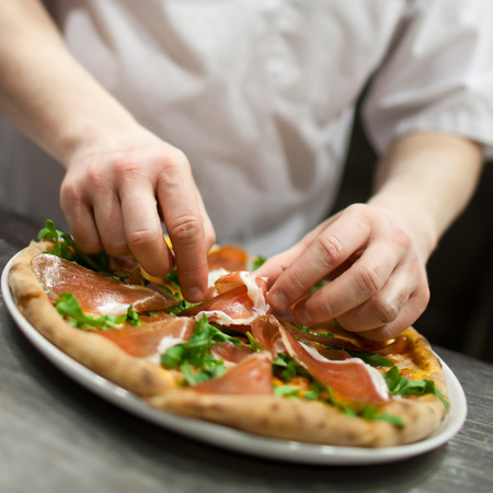 Closeup hand of chef baker in white uniform making pizza at kitchen Standard-Bild