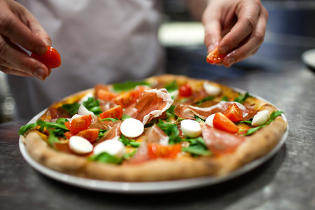 meal preparation: Closeup hand of chef baker in white uniform making pizza at kitchen Stock Photo