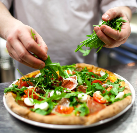 preparing food: Closeup hand of chef baker in white uniform making pizza at kitchen Stock Photo
