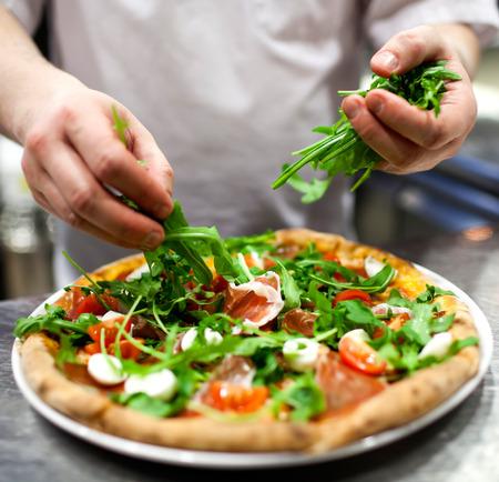 cooking: Closeup mano de baker de cocinero en uniforme blanco haciendo pizza en cocina