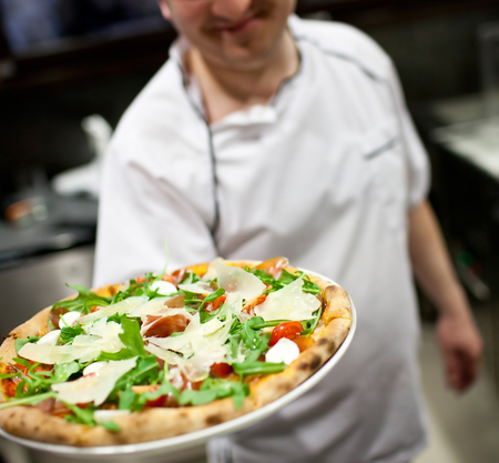 hoagie: The waiter of restaurant with a pizza in hands Stock Photo
