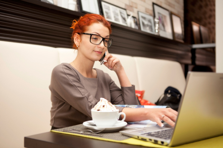 Businesswoman sitting at table in cafe using notebook. Iced coffee stands in the foreground photo