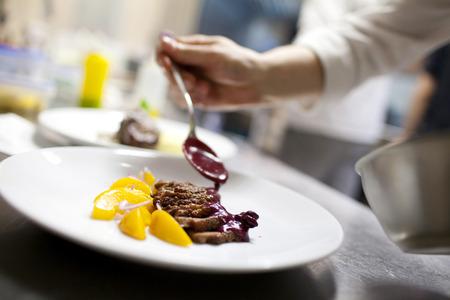 comida gourmet: El cocinero está adornando el plato delicioso desenfoque de movimiento en las manos Foto de archivo