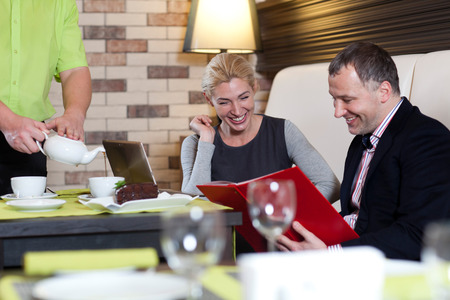 couple dining: happy couple dining out in restaurant and reading menu Stock Photo