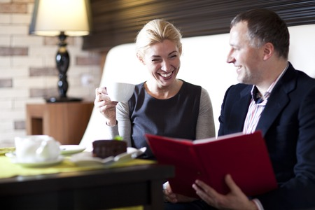 happy couple dining out in restaurant and reading menu Stock Photo