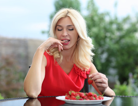 strawberry blonde: Blonde beautiful girl laughing eating and playing with fresh strawberry