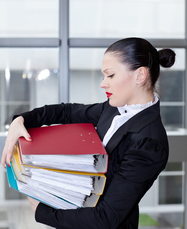 stu: Tired secretary with a lot of documents Stock Photo