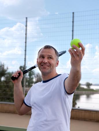 racquet: Male tennis player holding racquet on hard court Stock Photo