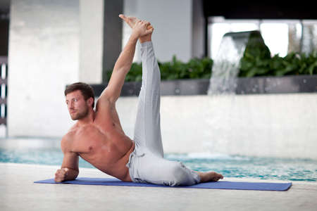 Man at the gym doing stretching exercises on the floor Stock Photo