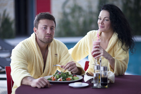 bathrobes: Cute couple in bathrobes having breakfast together at hotel