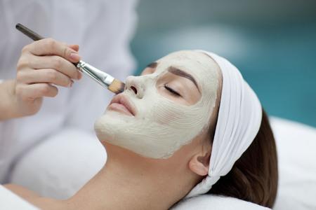 Primer plano de la bella joven con una toalla en la cabeza aplica la máscara facial