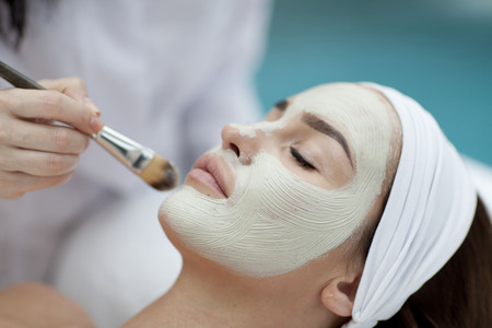 Close-up portrait of beautiful girl with a towel on her head applying facial mask Stock Photo