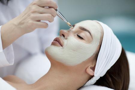 Close-up portrét krásné dívky s ručníkem na hlavě použití masky Reklamní fotografie