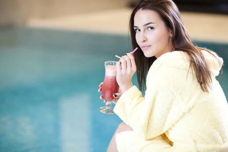 Woman with glass of cocktail enjoying wellness and spa swimming pool.