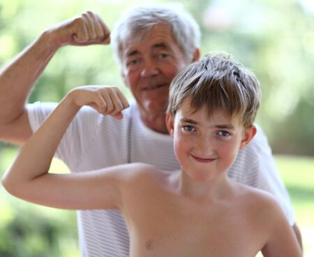 Grandfather and grandson flexing biceps. In The park on the nature Stock Photo