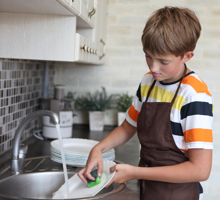 boy doing the dishes in the kitchen
