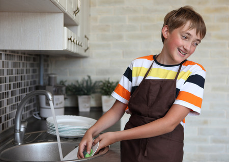 homemaker: boy doing the dishes in the kitchen