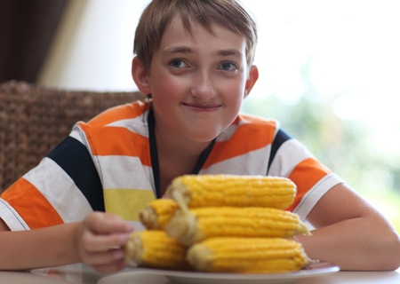 Portrait of a boy at the table with a plate of corn